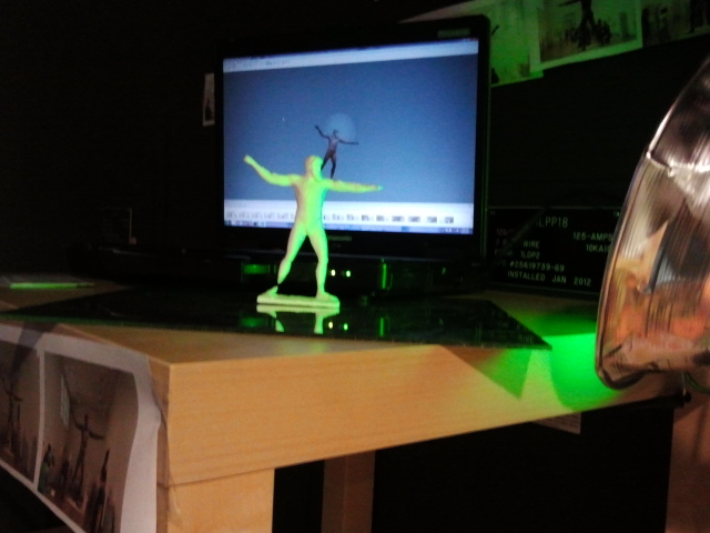 Our 3D printed action figure of the Artemision Bronze in front of a screen showing the 3D model we built him from.